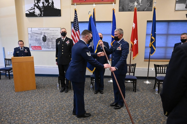 Brig. Gen. Darrin Anderson accepts a symbolic flag staff representing his assumption of responsibility for the position of North Dakota assistant adjutant general for Air from another Airman who is handing him the flag staff during a formal ceremony at the North Dakota Air National Guard Base, Fargo, N.D., April 10, 2021. A party of dignitaries watch the ceremony as they stand behind him.
