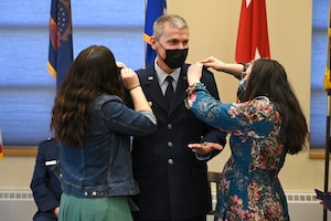 Brig. Gen. Darrin Anderson stands in service dress blue jacket between his daughters as they pin his new rank on the shoulders of his uniform.