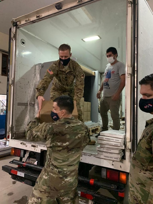 Three men in military uniforms and another in civilian clothes unload a refrigerated truck.
