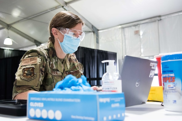 U.S. Air Force Maj. Helena Guerra, 22nd Medical Group bravo flight commander, prepares her station for her next COVID-19 vaccine patient April 28, 2021, at the Community Vaccination Center (CVC) in St. Paul, Minnesota. The total-force team consists of approximately 140 Airmen from 24 installations across the country. (U.S. Air Force photo by Senior Airman Alexi Bosarge)
