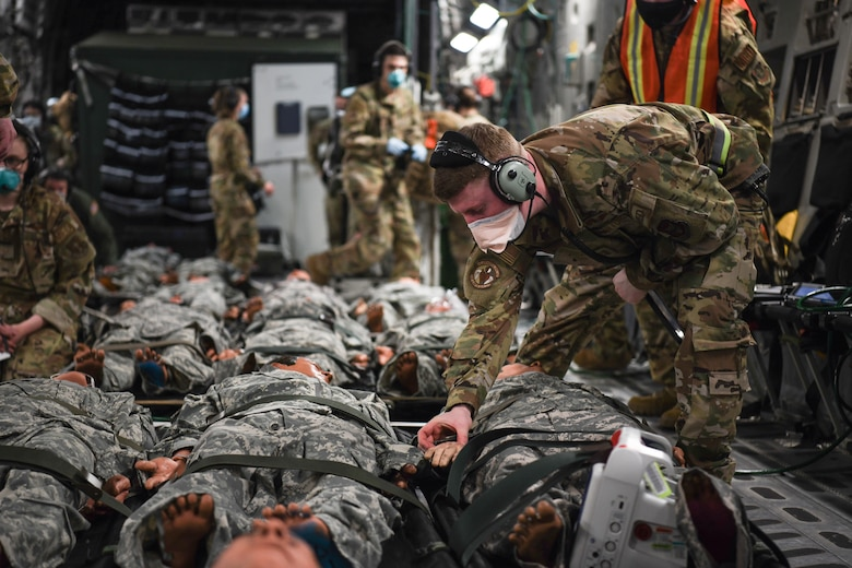 Senior Airman Nathan Boyer, 445th Aeromedical Evacuation Squadron, checks the vitals of patients on a 445th Airlift Wing C-17 Globemaster III during the Ultimate Caduceus training exercise April 29, 2021.  U.S. Transportation Command (USTRANSCOM) began a week-long aeromedical and global patient movement exercise, Ultimate Caduceus, April 26. Approximately 250 personnel including members of the 445th Airlift Wing and the 88th Air Base Wing participated in the field training exercise. (U.S. Air Force photo//Master Sgt. Patrick O'Reilly)