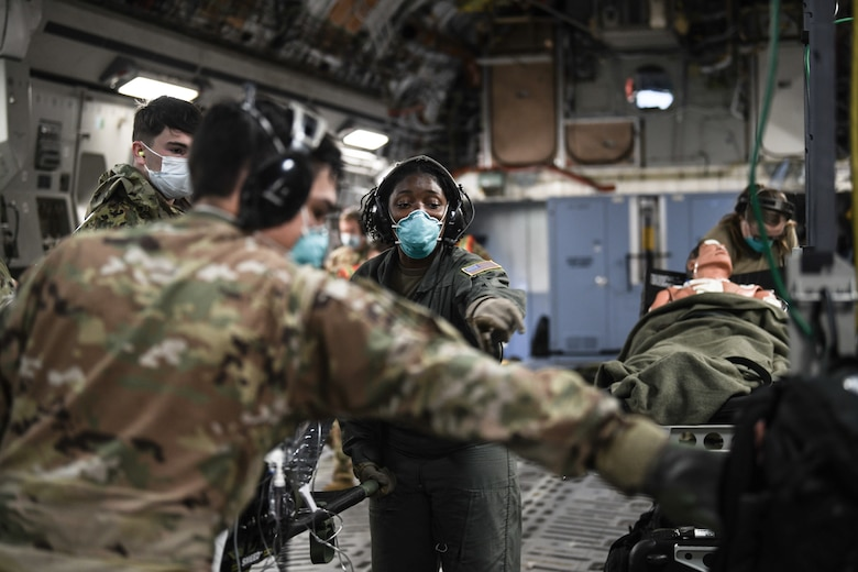 Senior Airman Shirneal Burnside, 445th Aeromedical Evacuation Squadron, gives direction to Airmen transporting patients onto a 445th Airlift Wing C-17 Globemaster III during the Ultimate Caduceus training exercise April 29, 2021. U.S. Transportation Command (USTRANSCOM) began a week-long aeromedical and global patient movement exercise, Ultimate Caduceus, April 26. Approximately 250 personnel including members of the 445th Airlift Wing and the 88th Air Base Wing participated in the field training exercise. (U.S. Air Force photo//Master Sgt. Patrick O'Reilly)
