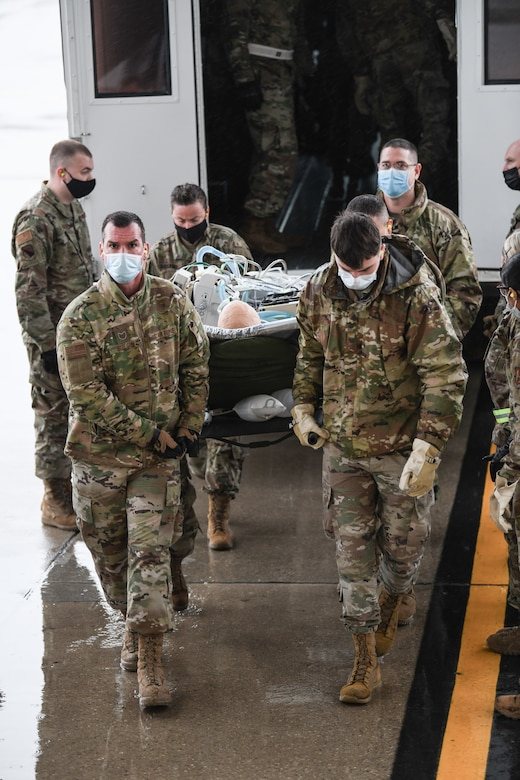 """Medical personnel from Wright-Patterson Air Force Base, Ohio, transport """"patients"""" onto a 445th Airlift Wing C-17 Globemaster III during the Ultimate Caduceus training exercise April 29, 2021.   U.S. Transportation Command (USTRANSCOM) began a week-long aeromedical and global patient movement exercise, Ultimate Caduceus, April 26. Approximately 250 personnel including members of the 445th Airlift Wing and the 88th Air Base Wing participated in the field training exercise. (U.S. Air Force photo//Master Sgt. Patrick O'Reilly)"""