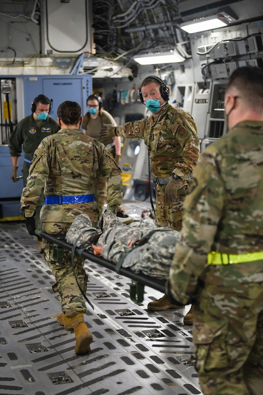 Senior Airman Nathan Boyer, 445th Aeromedical Evacuation Squadron, gives direction to Airmen transporting patients onto a 445th Airlift Wing C-17 Globemaster III during the Ultimate Caduceus training exercise April 29, 2021. U.S. Transportation Command (USTRANSCOM) began a week-long aeromedical and global patient movement exercise, Ultimate Caduceus, April 26. Approximately 250 personnel including members of the 445th Airlift Wing and the 88th Air Base Wing participated in the field training exercise. (U.S. Air Force photo//Master Sgt. Patrick O'Reilly)