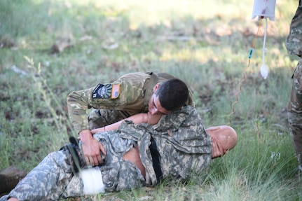 Spc. Adam Barlow, from the 65th Field Artillery Brigade, Utah National Guard, evaluates and treats a simulated casualty July 20, 2021, during the U.S. Army National Guard Best Warrior Competition at Camp Navajo Military Reservation, Arizona.
