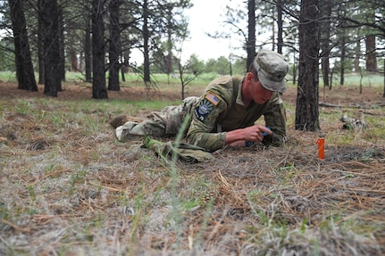 Spc. Adam Barlow, from the 65th Field Artillery Brigade, Utah National Guard, sets up a simulated claymore mine July 21, 2021, during the U.S. Army National Guard Best Warrior Competition at Camp Navajo Military Reservation, Arizona.
