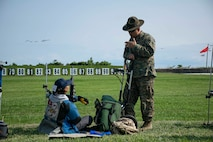A U.S. Marine with the United States Marine Corps (USMC) Shooting Team, coaches a junior shooter with the Civilian Marksmanship Program (CMP) during the USMC Shooting Team's Junior Clinic at Camp Perry, Ohio, July 31, 2021. The purpose of the clinic was for the USMC Shooting Team to teach junior shooters with the CMP the fundamentals and safety procedures of competitive shooting. (U.S. Marine Corps photo by Cpl. Nello Miele)