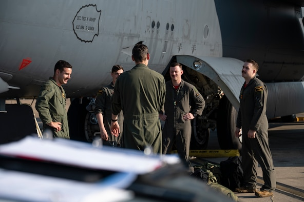 Five men stand in a circle near an airplane.