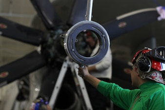 """Aviation Machinist's Mate Airman Luis Herrera-Chacon, right, from Santa Ana, El Salvador, Aviation Machinist's Mate Airman Jesse Barajas, left, from Perris Calif., and Aviation Machinist's Mate 2nd Class Joshua Smith Choctaw Okla., remove the propeller variable pitch actuator from an E-2D Hawkeye assigned to the """"Wallbangers"""" of Carrier Airborne Early Warning Squadron (VAW) 117 aboard the aircraft carrier USS Abraham Lincoln (CVN 72)."""