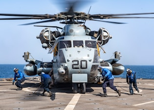 Sailors assigned to dock landing ship USS Carter Hall (LSD 50) chock and chain a CH-53E Sea Stallion helicopter attached to Marine Medium Tiltrotor Squadron (VMM) 162 (Reinforced) during routine flight operations in the Arabian Gulf.