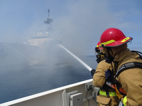Coast Guard Cutter Benjamin Bottoms crewmembers work with Coast Guard Cutters Haddock and Munro to extinguish a vessel fire off the coast of San Diego, July 15, 2021. The vessel left the Oceanside harbor heading towards Carlsbad when it was seen on fire.