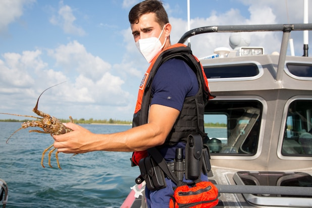 Petty Officer 3rd Class Leo Rojas holds a lobster after double checking the size of the lobster during the Sport Lobster mini season just off shore of Key West, Florida, July 28, 2021. The mini season is the last consecutive Wednesday and Thursday of July each year.