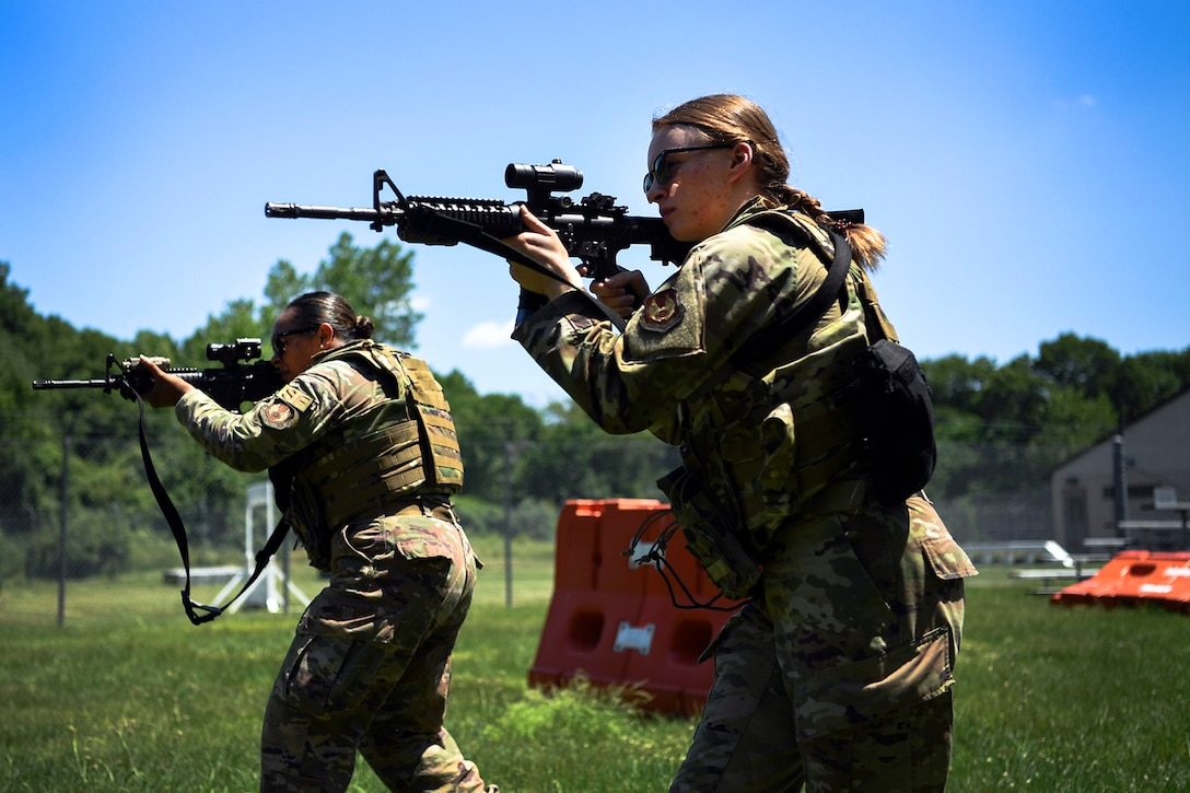 Two airmen wearing body armor carry weapons in a field.