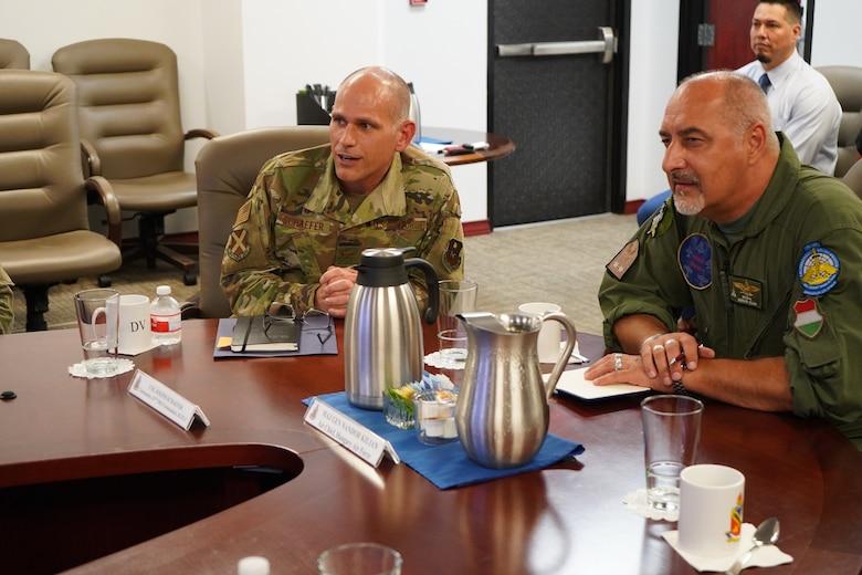 Col. Schaefer joins Maj. Gen. Kilian at conference table.