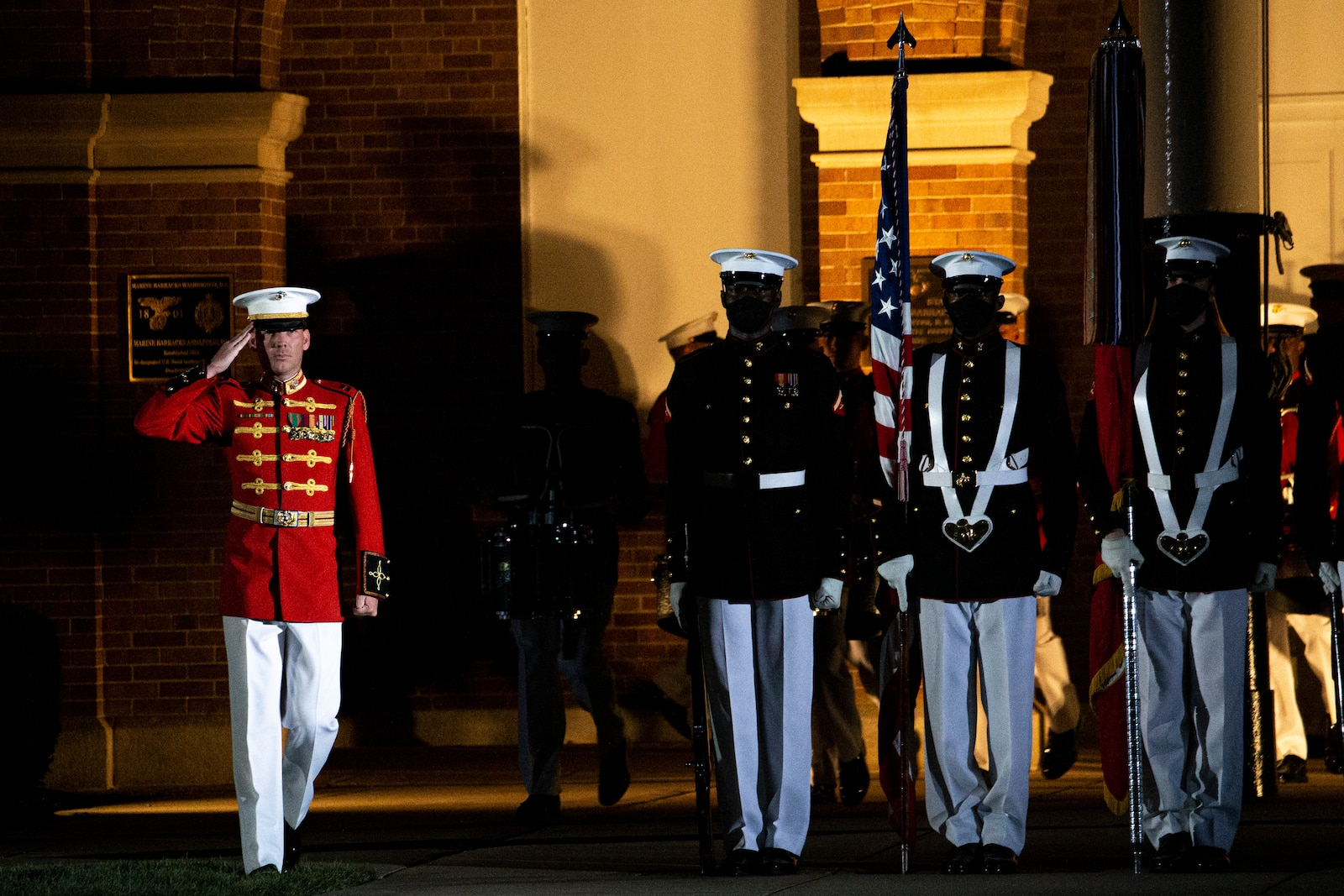 """Captain Nathan D. Morris, assistant director, """"The Commandant's Own,"""" U.S. Marine Drum and Bugle Corps, salutes the national ensign during the Friday Evening Parade at Marine Barracks Washington, July 30, 2021"""