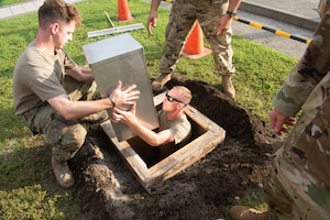 Airmen place a time capsule into a hole.