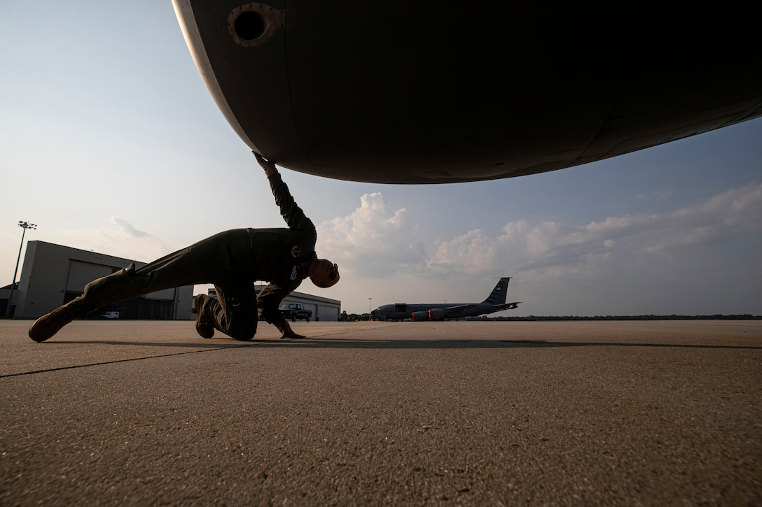 An airman kneels on the ground and looks up at an aircraft body.