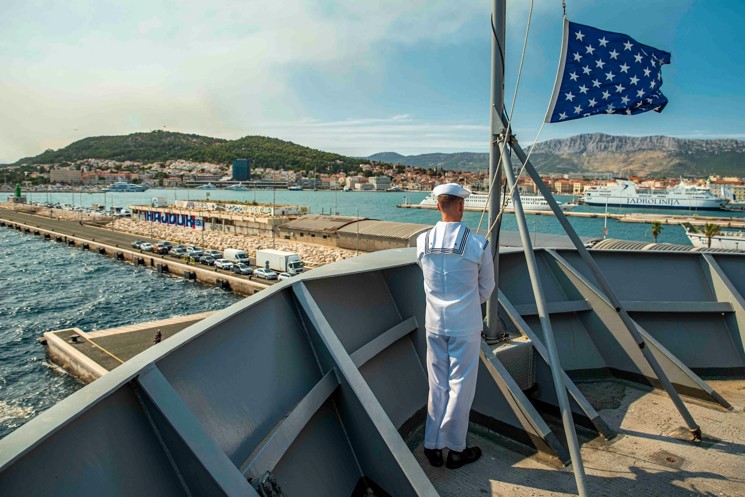 Hospital Corpsman 2nd Class Donald Coony lowers the ships Jack   aboard the Blue Ridge-class command and control ship USS Mount Whitney (LCC 20) as the ship gets underway from Split, Croatia, August 2, 2021. Mount Whitney is the U.S. Sixth Fleet flagship, homeported in Gaeta, and operates with a combined crew of U.S. Sailors and Military Sealift Command civil service mariners.