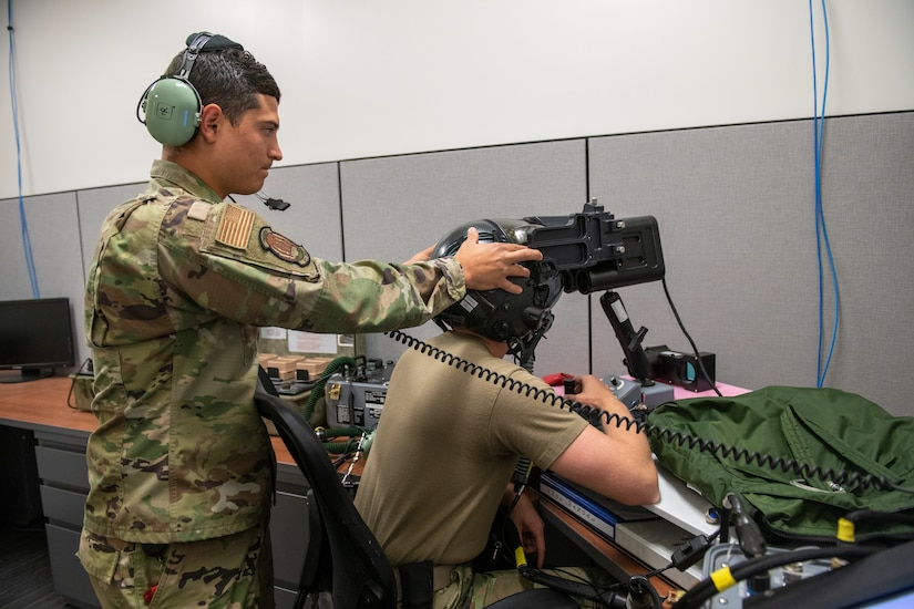 U.S. Air Force Staff Sgt. AJ Arteaga, 419th Operations Support Squadron, adjusts the head position of Tech. Sgt. Anthony Farnsworth, 419th OSS, during F-35 helmet optical fit training at Hill Air Force Base, Utah, on July 10, 2021. Reservists in the 419th OSS are responsible for maintaining and repairing pilot gear to ensure it is in proper working condition.