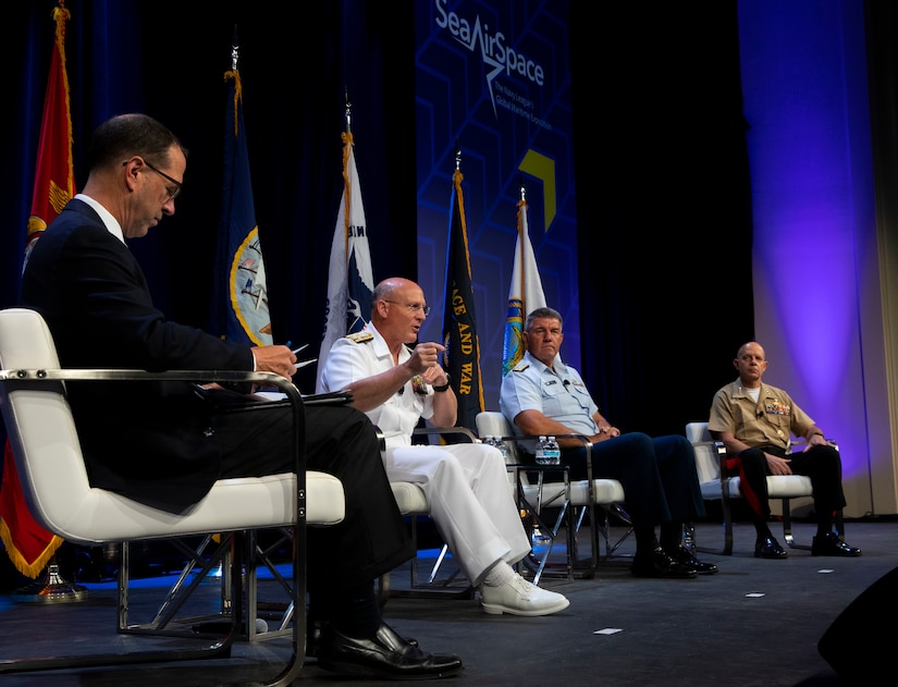 Navy admiral sits and speaks on a stage shared by other officials.