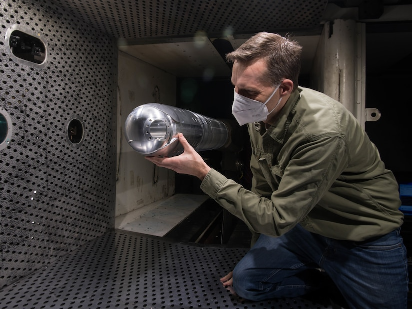 A researcher kneels and handles a metal tube-shaped device in a wind tunnel.