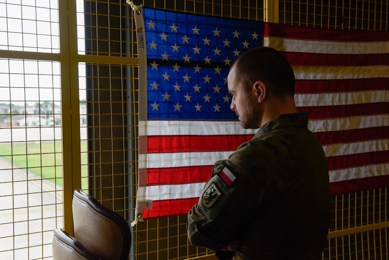 Polish army Lt. looks out of a window overlooking the flightline while visiting Ramstein Air Base, Germany, for Negatively Pressurized Conex Lite training
