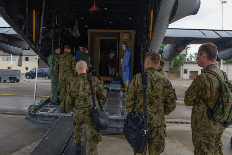 Members of the Polish army and air force observe U.S. Air Force Airmen conducting Negatively Pressurized Conex Lite training
