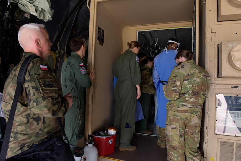 Polish army and air force members observe U.S. Air Force Airmen conducting Negatively Pressured Conex Lite training