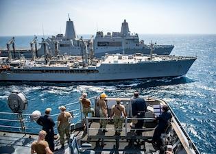 Sailors assigned to the dock landing ship USS Carter Hall (LSD 50) observe a replenishment-at-sea between the amphibious transport dock ship USS San Antonio (LPD 17), back, and the fleet replenishment oiler USNS Pecos (T-AO 197), middle.