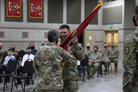 Maj. Barbara Blanke passes the guidon to 1st Sgt. Donnelly, the incoming first sergeant of HHD 640th Regiment, RTI, at Camp Williams, Utah, April 17, 2021