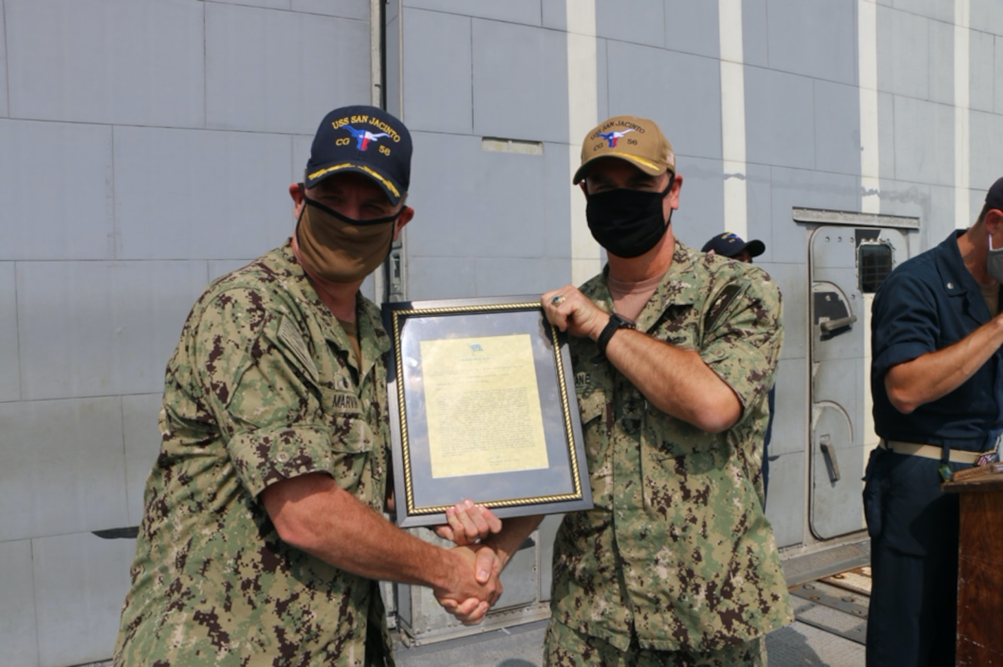 NAVAL STATION NORFOLK (Aug. 2, 2021) – Rear Adm. Brendan McLane, commander, Naval Surface Force Atlantic, presents Capt. Chris Marvin, commanding officer of the guided-missile cruiser USS San Jacinto (CG 56), with the Navy Unit Commendation. The crew of San Jacinto was awarded for their leadership and hard work in support of the Dwight D. Eisenhower Carrier Strike Group during their 2020 deployment, which lasted 206 days with no port visits. (U.S. Navy photo by Boatswain's Mate 3rd Class Danielle Bordine/Released)
