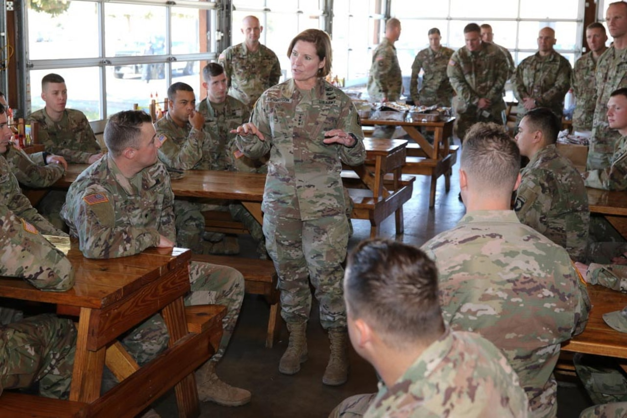 A woman dressed in a military uniform stands surrounded by service members, some sitting at wooden picnic tables and some standing.