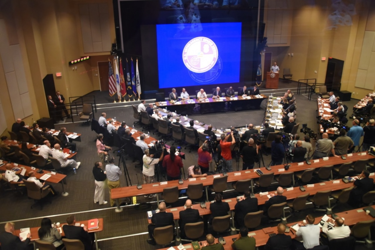 People are seated at tables in a large conference room; a large screen is in the center of the room.