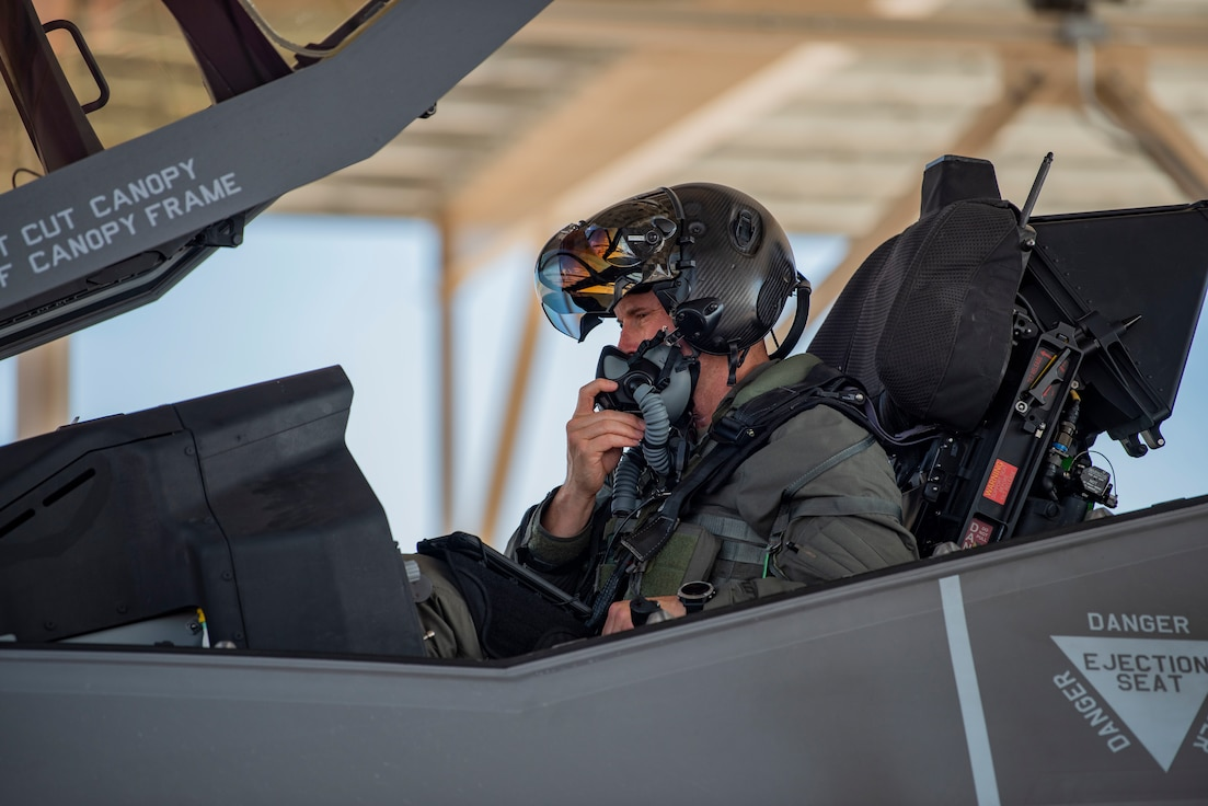 crew chief with hands in air with wrists crossed to the side of an F-35 on the flight line