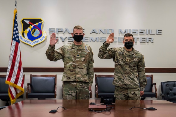 """U.S. Space Force Lt. Col. Randall Carlson, Space and Missile Systems Center capability integrator for missile warning, left, and Maj. Christopher Andrews, SMC missile warning enterprise integration chief, perform a ceremonial Oath of Office during a virtual transfer ceremony hosted by U.S. Space Force Chief of Space Operations Gen. John W. """"Jay"""" Raymond, at Los Angeles Air Force Base, California, Aug. 2, 2021. After the Oath of Office was administered, signifying a ceremonial transfer from the U.S. Air Force to the USSF, officers across the globe had the opportunity to engage with Raymond during a town hall. (U.S. Space Force photo by Staff Sgt. Elijah Jackson)"""