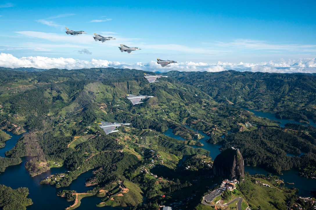 Jets fly in a V formation over mountainous terrain.