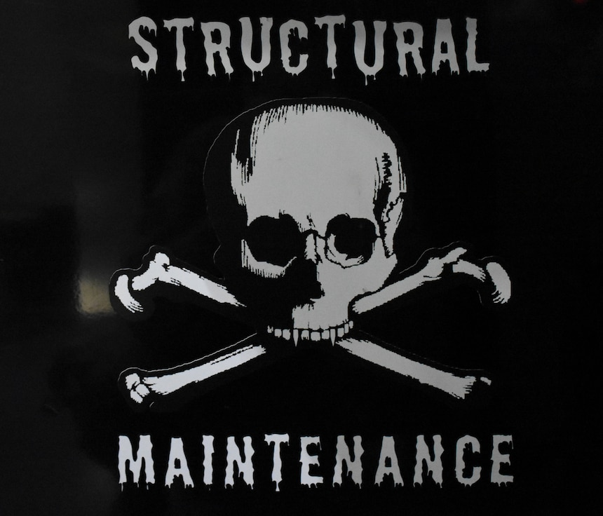 A structural maintenance sticker with a skull and crossbones on the side of a black rolling toolbox.