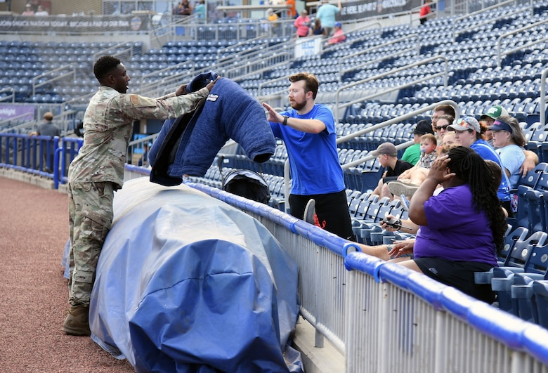 """U.S. Air Force Staff Sgt. Victor Henderson, 81st Security Forces Squadron military working dog handler, shows attendees a bite suit following a military working dog demonstration at the MGM Park during a Biloxi Shuckers Minor League Baseball team pre-game festivities in Biloxi, Mississippi, Aug. 1, 2021. The """"Bark in the Park"""" themed baseball game invited fans to attend the game with their dogs. (U.S. Air Force photo by Kemberly Groue)"""