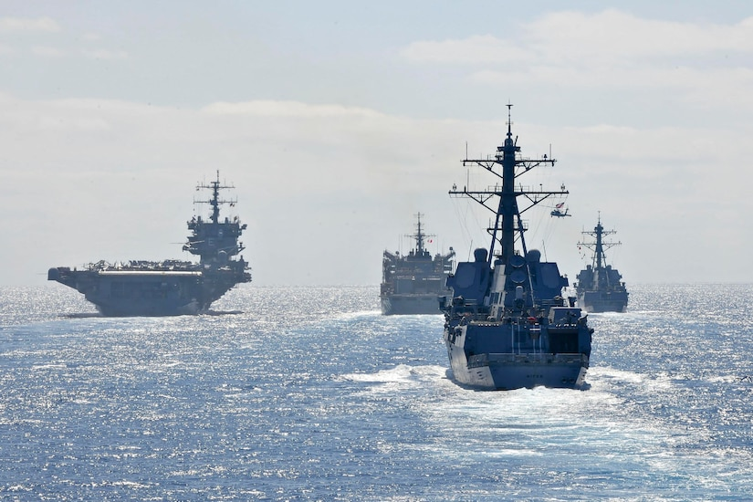 Military ships move together through the ocean.