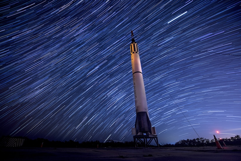 Stars move through a night sky.  A rocket is on display.