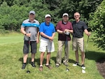 Four men in stand together holding golf clubs.
