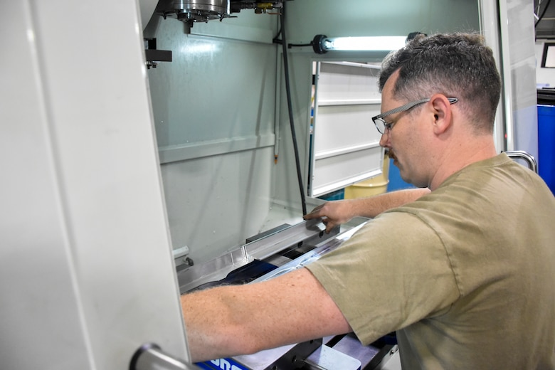 U.S. Air Force Staff Sgt. Johnathan Shellhart, a machinist with the 442d Maintenance Squadron, places a piece of stock into a CNC mill