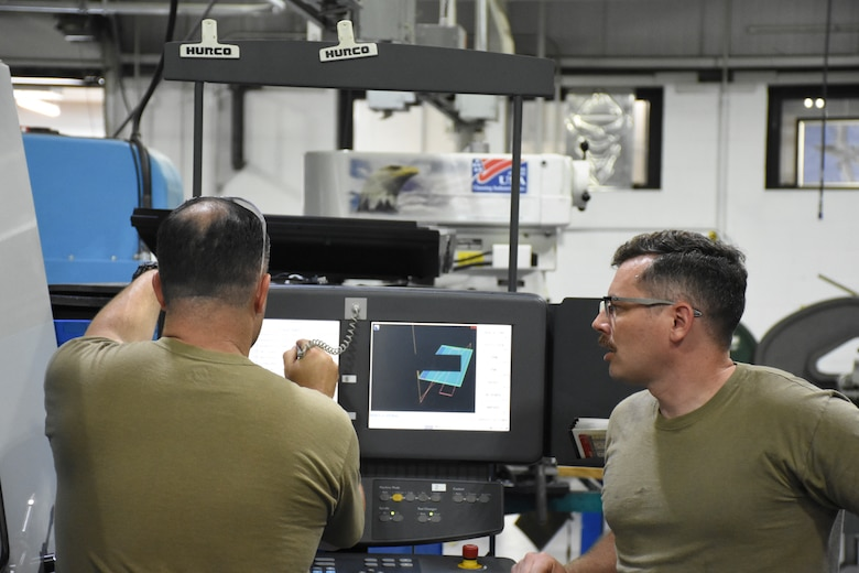 Master Sgt. Cameron Williams, left, and Staff Sgt. Johnathan Shellhart, both machinists with the 442d Maintenance Squadron, design a part on computer-aided drafting software.
