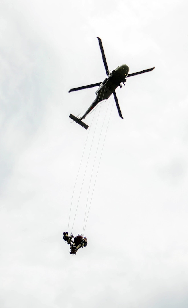 A Colombian army UH-60 Black Hawk carries two members of the Colombian army search and rescue team