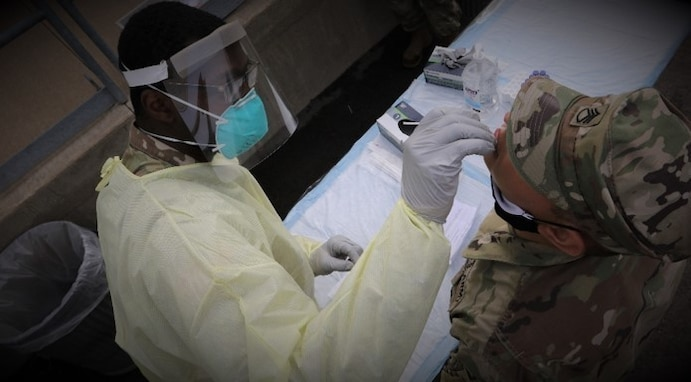 A combat medic specialist with the 329th Medical Company from Fairview, Pa performs BinaxNOW testing on a deploying soldier during Pershing Strike 21 at Fort McCoy, Wis.
