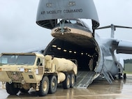 The 641st Regional Support Group from St. Petersburg, FL in coordination with the Arrival/Departure Airfield Control Group download a HEMTT Tanker from a C-5 Galaxy during Pershing Strike 21 at Fort McCoy, Wis.