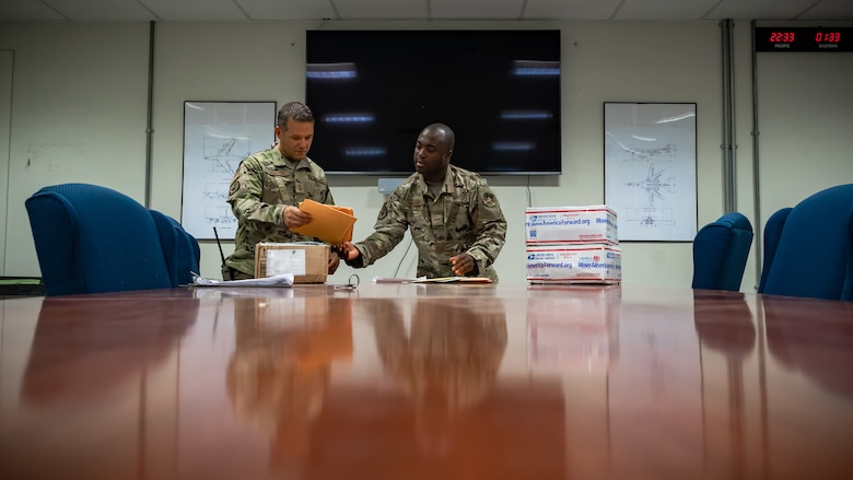 Senior Airman Ajay Vogar, 379th Expeditionary Maintenance Squadron commander support staff security manager, hands a piece of mail to Chief Master Sgt. Jason Thompson, 379th EMXS lead production superintendent at Al Udeid Air Base, Qatar, July 27, 2021.