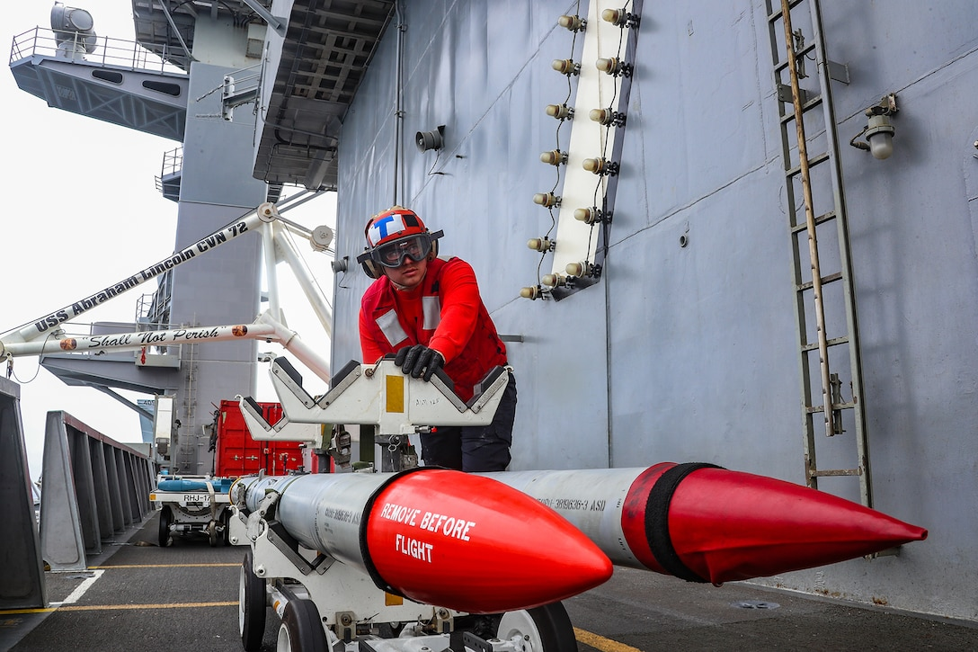 An airman uses a carrier to move two red-tipped rockets on board a ship.