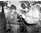 Marine Pfcs. Preston Toledo and Frank Toledo, both Navajo Code Talkers and cousins, relay orders in the Navajo language on a field radio. They were attached to a Marine artillery regiment in the South Pacific. This photo was taken July 7, 1943.