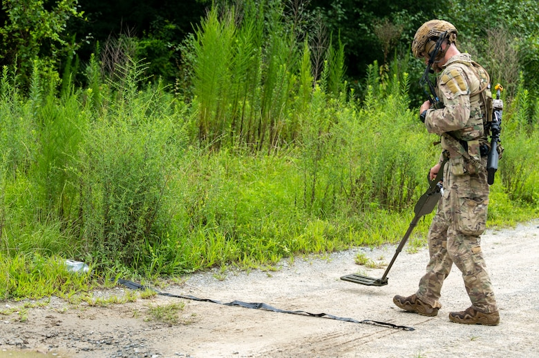 Senior Airman Joseph Plato, 4th Civil Engineer Squadron explosive ordnance disposal technician, uses a digital hand-held metal detector as he approaches a training roadside improvised explosive device during field training exercise Operation Guillotine at Seymour Johnson Air Force Base, North Carolina, July 27, 2021.